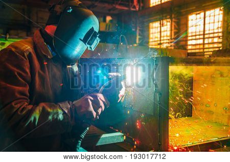 The worker in overalls and a protective mask welds metal with a welding machine. Profession welder. Man in protective overalls.
