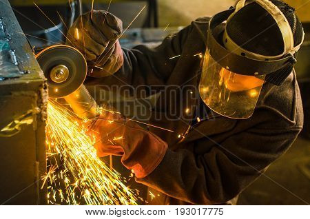 A man in working form and a face mask cuts a metal saw with a Bulgarian on the background of a metallurgical industrial plant.