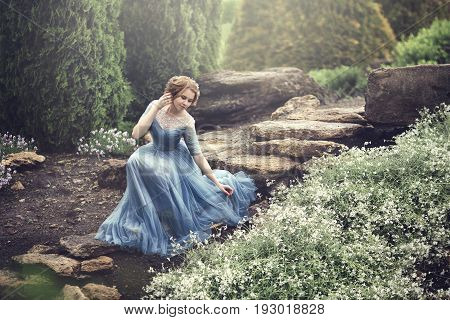 Beautiful young girl in a blue dress as a cinderella is walking in the garden. Sits on the stairs near the flowers. poster