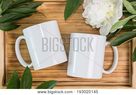Two white mugs cups wedding mockup. Peony green leaves wooden background. Summer gifts boho style