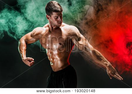Handsome man with muscular topless body holding arm down. Smoke. Isolated.