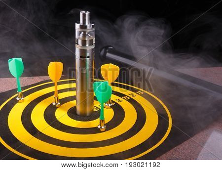 Magnetic green and yellow dart arrows and electronic cigarette within vapor on yellow dart board. black background