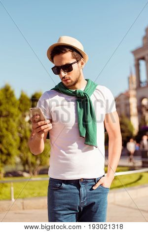 Weekend Out. Young Handsome Brunet Is Browsing On His Pda While Walking Outdoors On A Summer Day. Ve