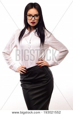 Portrait of a beautiful young woman secretary in glasses white blouse and black skirt on white wall background