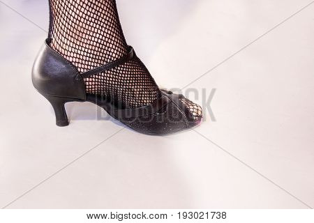 Woman dancing with black salsa sandals. Night club