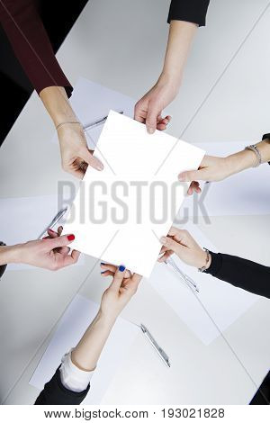 In the office a workgroup composed of five women in a circle holding a blank sheet above a desk