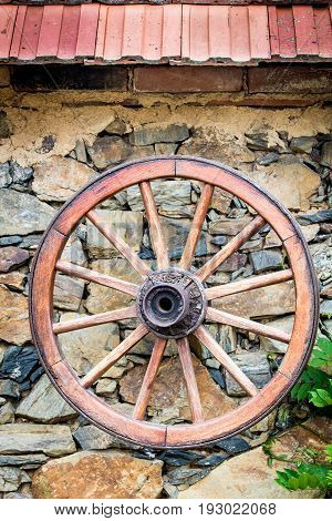 Old wooden Cartwheel on the stone wall