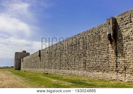 Aigues-Mortes old town stone wall outside green grass blue sky