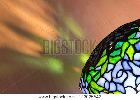 Colorful stained glass light reflections on a pink shabby chic bedroom wall at night time from a decorative lampshade. Close up diagonal perspective.