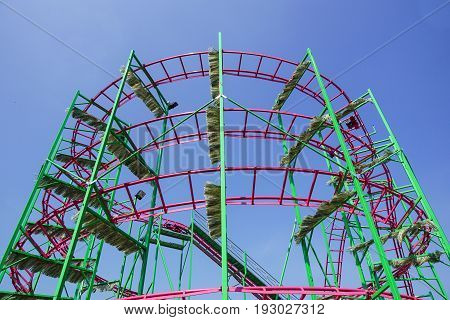 Rollercoaster track against a brilliant blue sky .