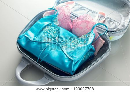 Packing clothes into travel bag - Luggage and people concept