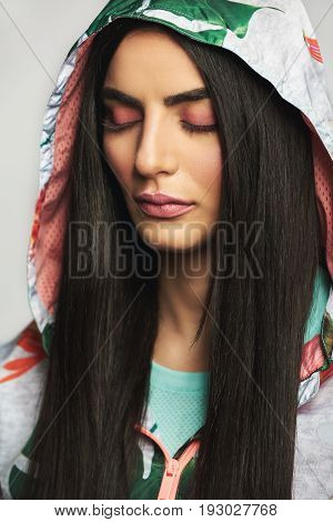 Young Woman Wearing Hood Standing With Eyes Closed