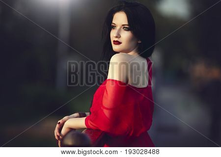 Portrait of a mysterious brunette beautiful woman with red lips and dress. He admires the sunset in the city.