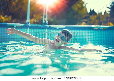 Happy little kid swimming in pool outdoor color graded sunset
