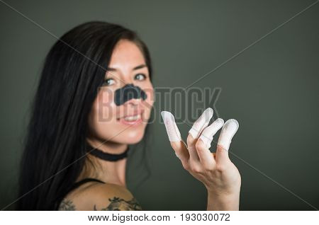 Close up of young woman wearing nails protector in her nails and a nose mask to clean skin from black spots, in a black background.