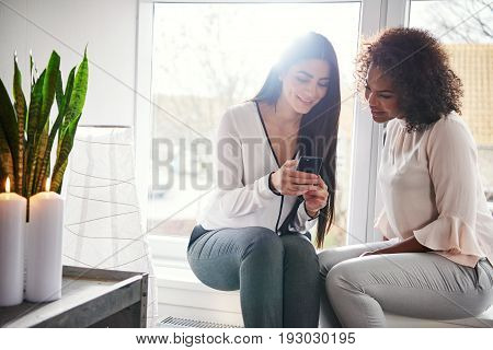 Two Young Woman Reading An Sms On A Mobile
