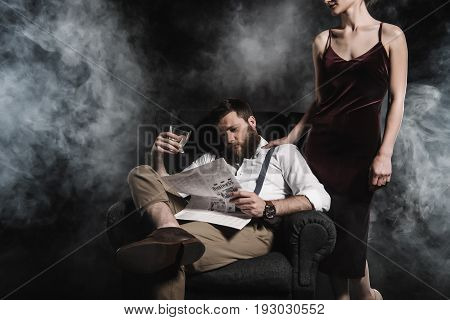 stylish man holding whisky glass and reading newspaper while woman standing near him