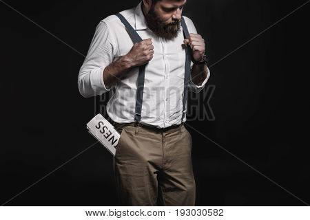 Stylish Man In White Shirt And Suspenders Standing With Business Newspaper In Pocket Isolated On Bla