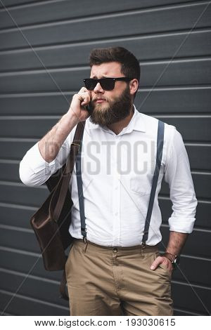 Stylish Man In Sunglasses And Suspenders Using Smartphone And Looking Away