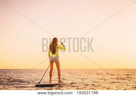 Slim young woman on stand up paddle board with beautiful sunset or sunrise colors