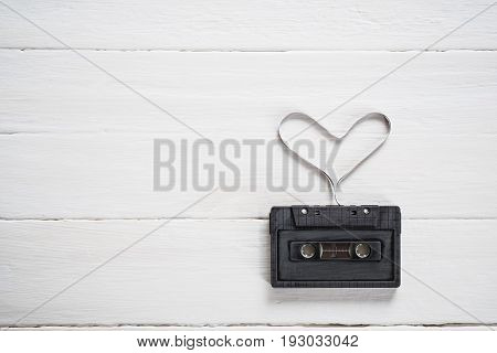 heart shape from cassette tape on vintage background, top view