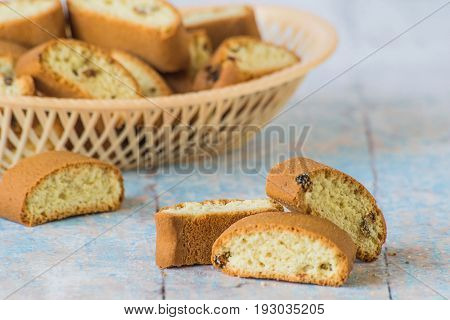 Homemade rusks with raisins in a small plastic basket on a blue wooden background.