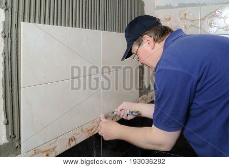 Tiler is installing a ceramic tile on a wall in a bathroom.