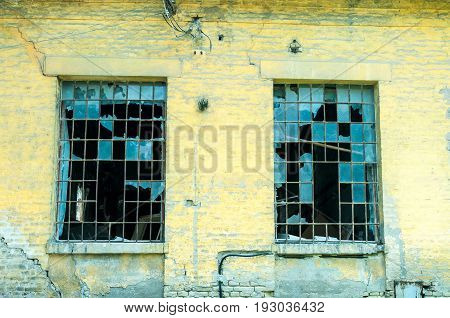 Old rustic facade of abandoned building with broken windows. Exterior wall of abandoned building.