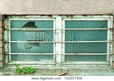 Dirty basement window with broken glass and safety metal gratings.