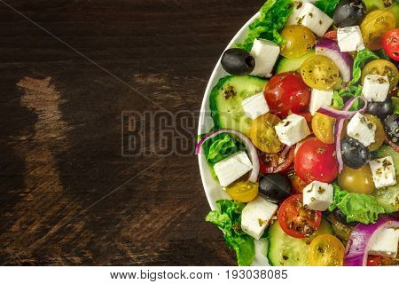 A closeup photo of a plate of Greek salad, with feta cheese, fresh vegetables, and olives, on a dark rustic texture with a place for text
