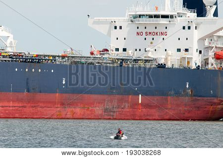 DELAWARE CITY, DE - AUGUST 1: View of an Oil tanker ship coming into port on Delware river on a background of blue sky on August 1, 2015
