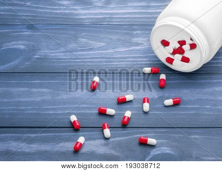 pills in a white jar on a wooden backgroun