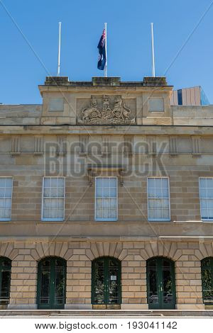 Hobart Australia - March 19. 2017: Tasmania. Central part of beige stone facade of Parliament House showing emblem and motto of British monarchs. Flag on top in blue sky.