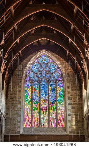 Hobart Australia - March 19. 2017: Tasmania. Large multicolor stained gothic window presenting nativity scene with beige stone wall and dark brown wood ceiling. Contemporary design with pastel colors.