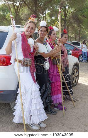 El Rocio Spain - June 1 2017: Group of female pilgrims in traditional spanish flamenco dress making a break on the road to El Rocio during the Romeria 2017. Andalusia Spain