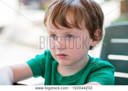 view of young little boy sitting down outside