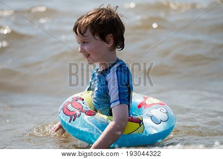 view of young boy floating in inner tubes in a blissful state