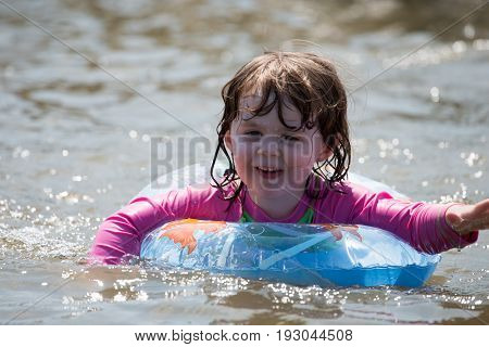 view of young girl floating in inner tubes in a blissful state