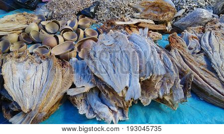 Stacks of dried fish filets and squash bowls on blue background on market day, Oaxaca, Mexico.