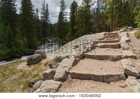 A cool hiking path with built in steps lined with rocks climbing along a roaring creek in the high country wilderness.