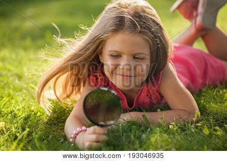 Girl nature young exploring magnifying glass lawn curiosity