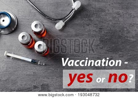 Vaccination debate concept. Vials and syringe with vaccine on gray background