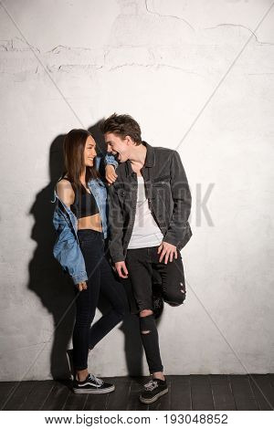 Picture of happy young hipster loving couple looking aside over gray background