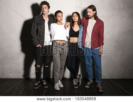 Image of concentrated young hipsters friends standing over gray background.