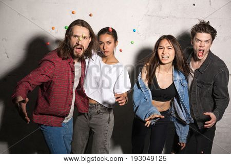 Picture of young angry hipsters loving couples standing over gray background scatter candies. Looking camera.