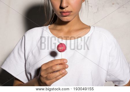 Cropped picture of young hipster woman standing over gray background holding candy.