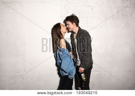 Picture of young hipster loving couple standing over gray background eating chocolate.
