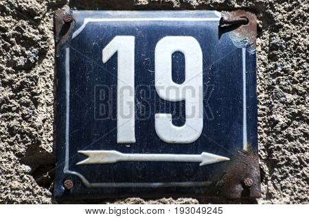 Weathered grunge square metal enameled plate of number of street address with number 19 closeup