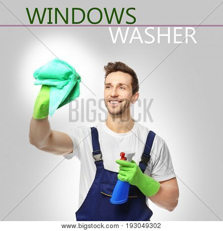 Young window cleaner with supplies on gray background