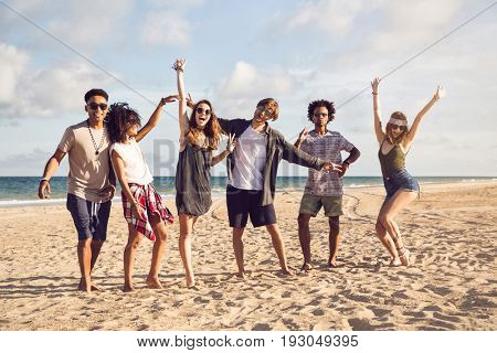Multiracial group of friends enjoying a day at beach and jumping